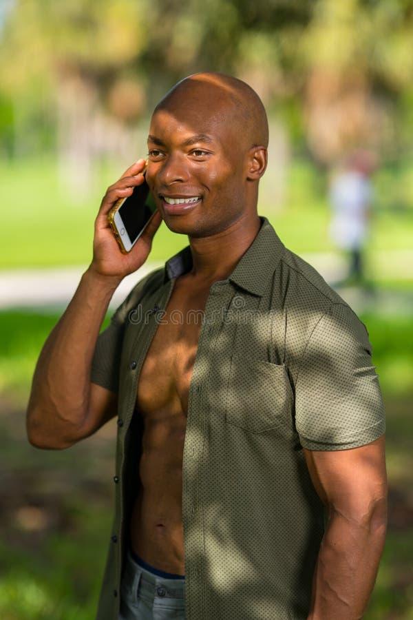 Parkerar den lyckliga afrikansk amerikanmannen för ståenden som talar på telefonen utomhus i, inställningen arkivbilder