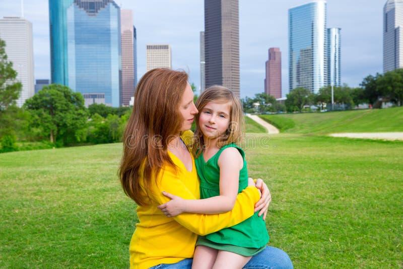 Parkerar den lyckliga kramen för modern och för dottern in på stadshorisont royaltyfri foto