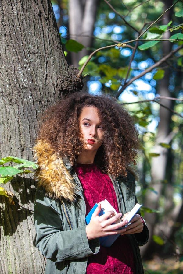 Parkerar den tonåriga flickaläseboken för lockigt hår i höst fotografering för bildbyråer