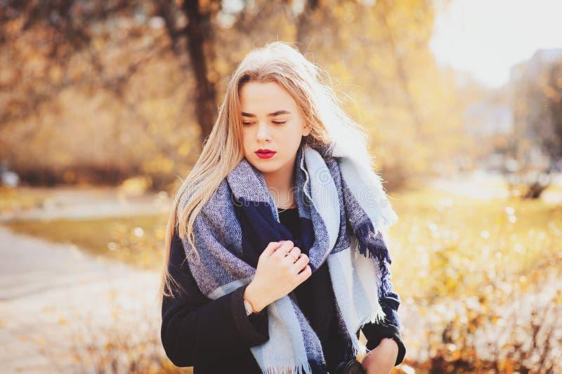 Parkerar den utomhus- tillfälliga ståenden för hösten av den unga härliga kvinnan som in går, i varm modedräkt royaltyfri foto