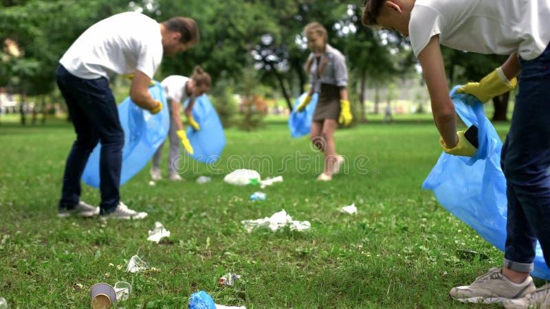 Parkerar den vänliga familjen organiserade rengörande dagen som ska göras ren, av hushållavskräde royaltyfri foto