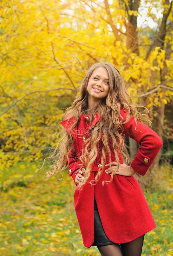 Parkerar det iklädda röda laget för modekvinnan i höst royaltyfri bild
