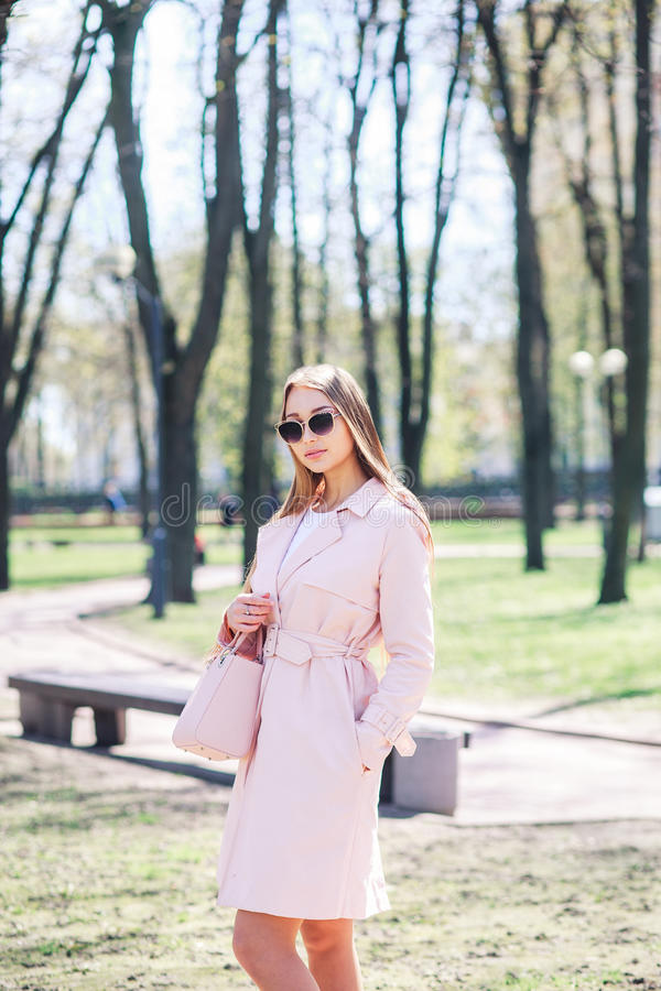 Parkerar det utomhus- fotoet för mode av den härliga unga kvinnan med blont hår i elegant kläder och solglasögon som poserar i so arkivfoto