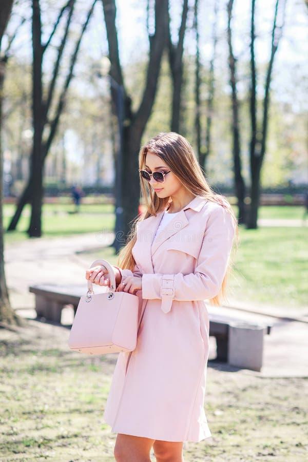 Parkerar det utomhus- fotoet för mode av den härliga unga kvinnan med blont hår i elegant kläder och solglasögon som poserar i so arkivbilder