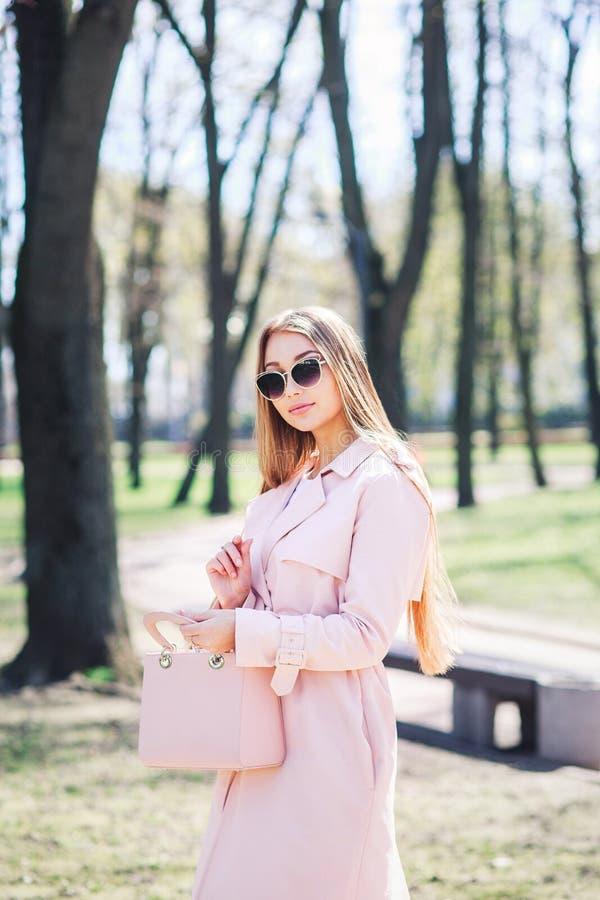 Parkerar det utomhus- fotoet för mode av den härliga unga kvinnan med blont hår i elegant kläder och solglasögon som poserar i so royaltyfria foton