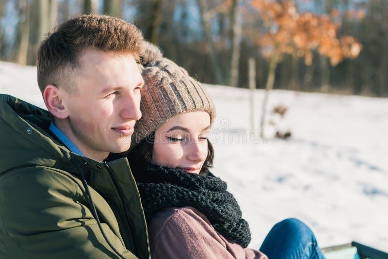 Parkerar förälskat sammanträde för härliga unga par på bänken på en klar solig dag Pojken och flickan tycker om värmen av vintern arkivfoto