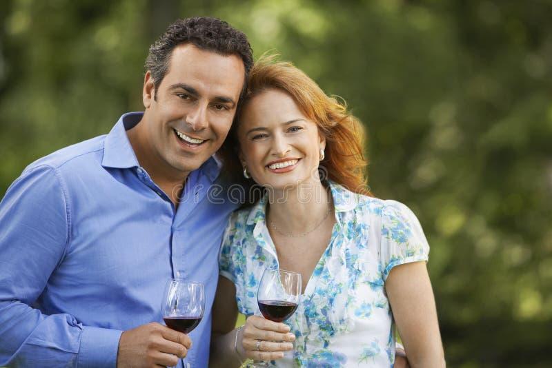 Parkerar hållande vinexponeringsglas för par in fotografering för bildbyråer