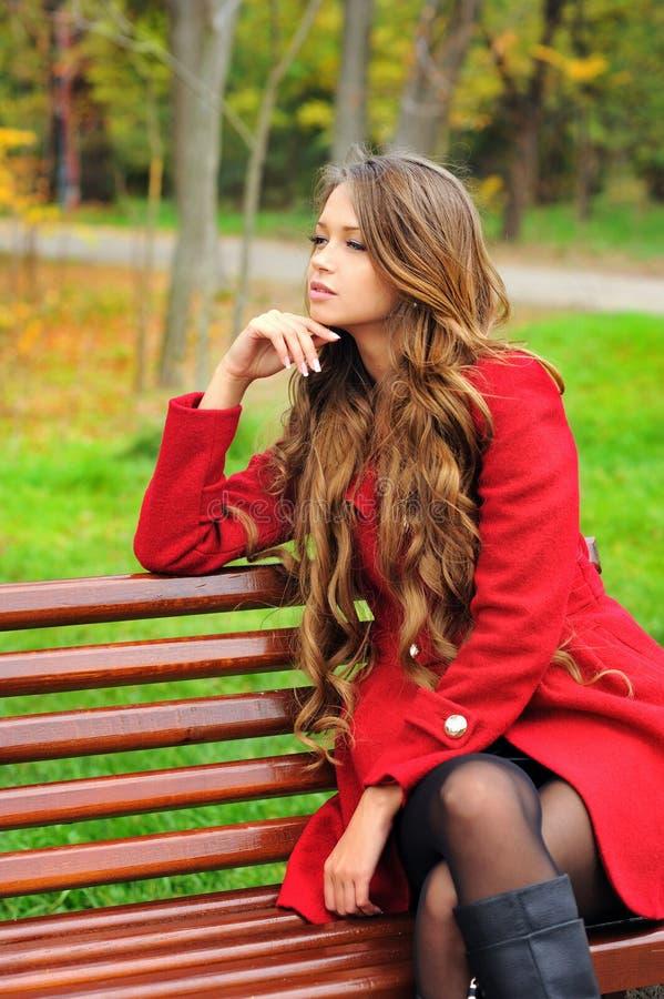 Parkerar iklätt rött lagsammanträde för kvinnan i höst arkivbild