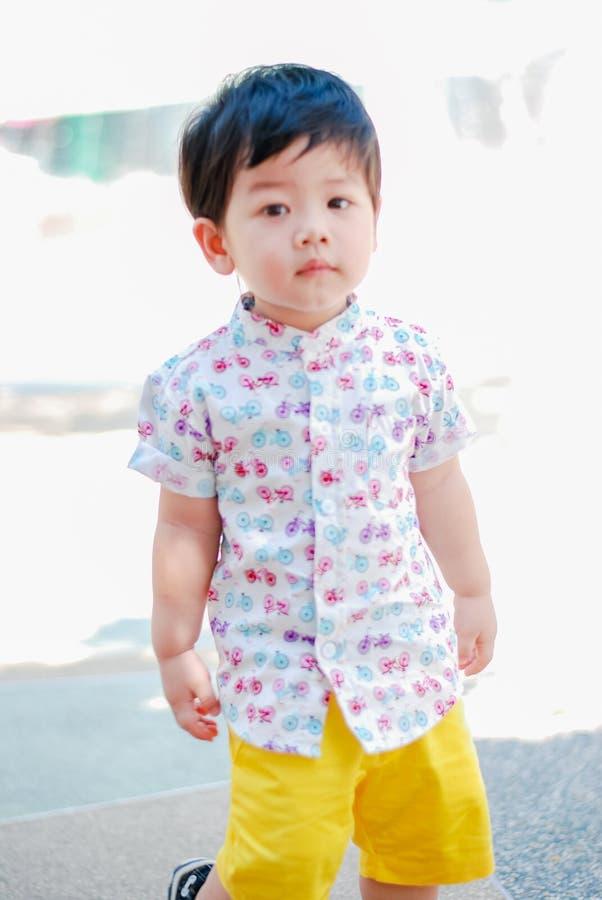 Parkerar lycklig smilling för gullig liten asiatisk pojke i utomhus, lyckliga ungar royaltyfri fotografi