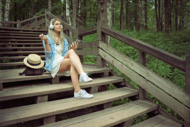 Parkerar lyssnande musik för härlig ung blond hipsterkvinna i hörlurar in med minnestavlan i händer som sitter på trämoment arkivfoto