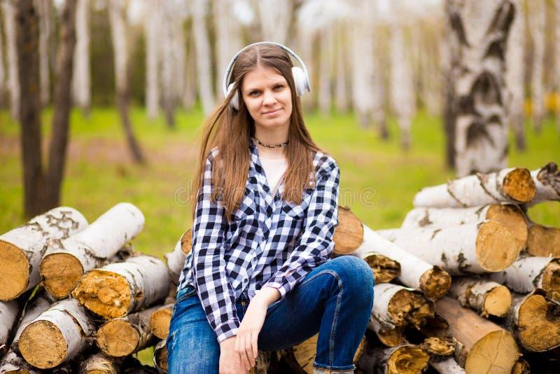 Parkerar lyssnande musik för nätt flicka med hennes hörlurar i sommar royaltyfri foto