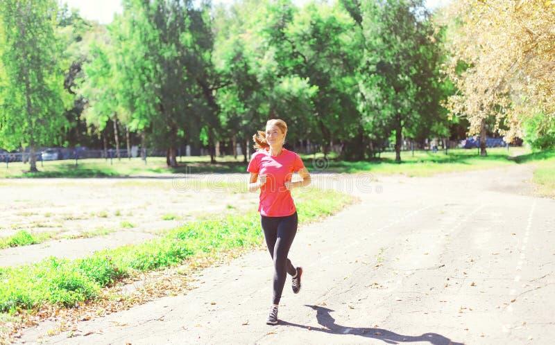 Parkerar spring för den unga kvinnan för kondition in, den kvinnliga löparegenomköraren, sporten och den sunda livsstilen royaltyfria foton