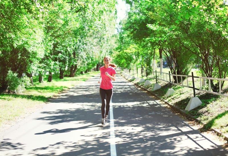 Parkerar spring för den unga kvinnan för kondition i sommar, den kvinnliga löparegenomköraren - sport och den sunda livsstilen royaltyfri bild