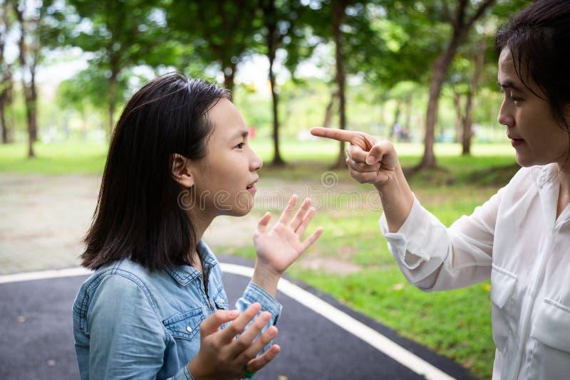 Parkerar uppfostrar den ilskna vuxna modern för Closeupståenden som grälar och att argumentera med den unga dottern i utomhus-, o royaltyfri foto