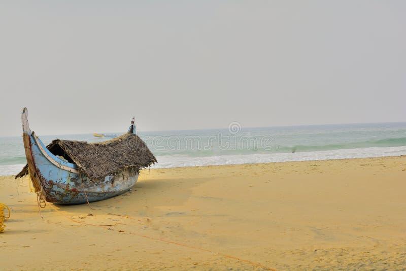 Parkerat: Fiskebåt med ett tak - på en strand arkivfoton