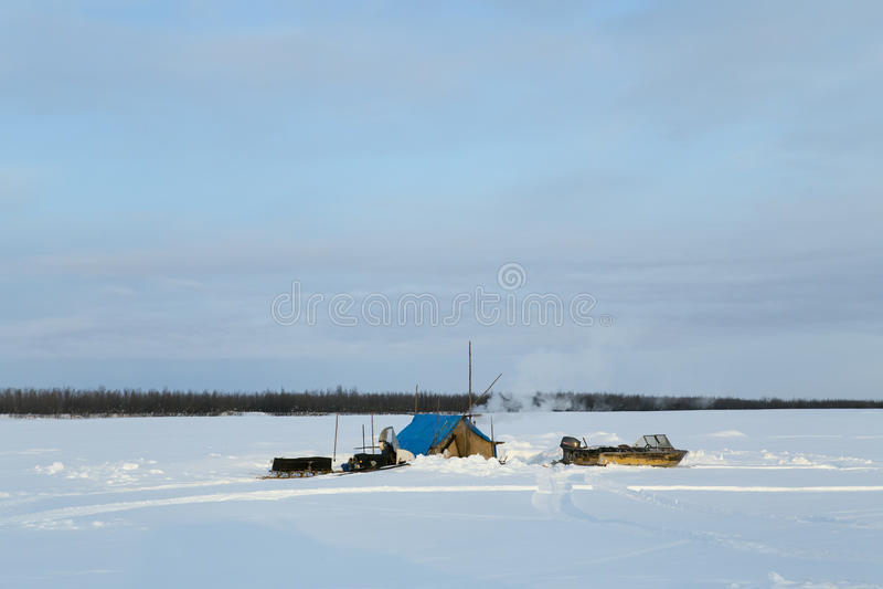 Parkeringsfiskare på en snöig flod royaltyfria bilder