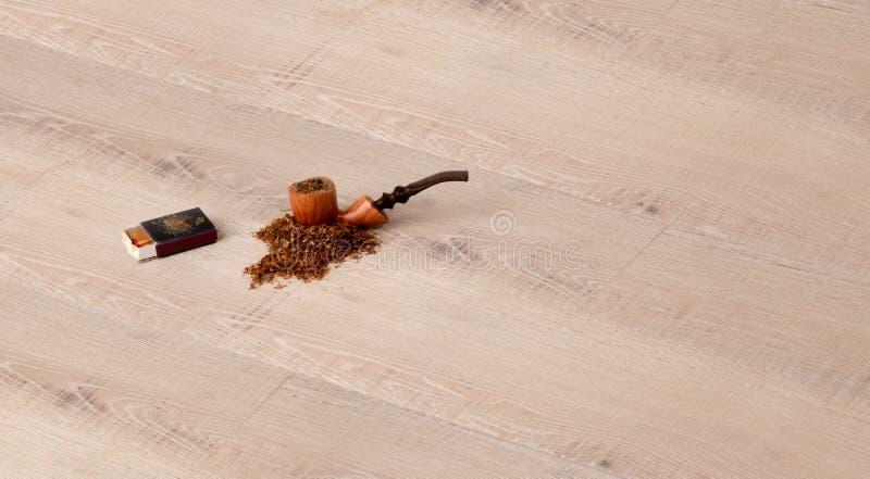 Parketbevloering met pijp, tabak en gelijken stock fotografie