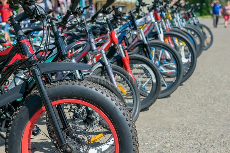 Parking of brand new teenager bicycles on asphalt, sale stock photo