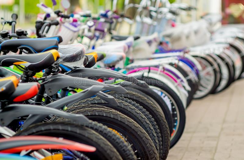 Parking of brand new teenager`s bicycles on asphalt, sale stock images