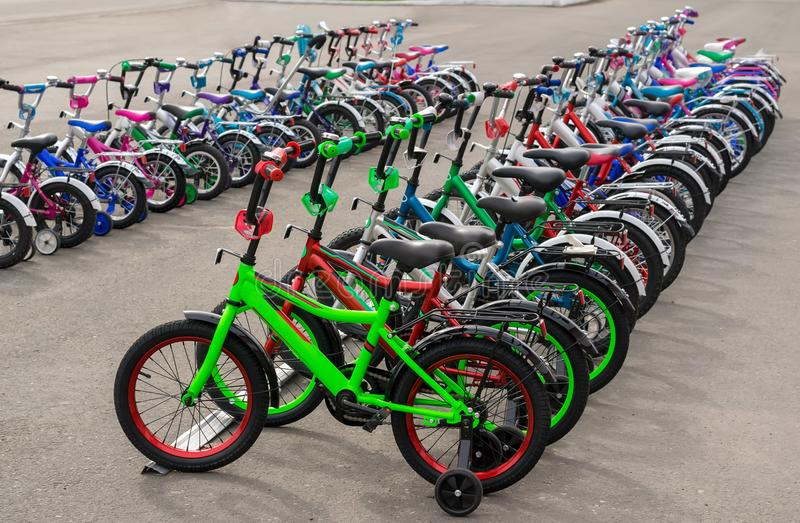 Parking of brand new teenager`s bicycles on asphalt, sale royalty free stock images