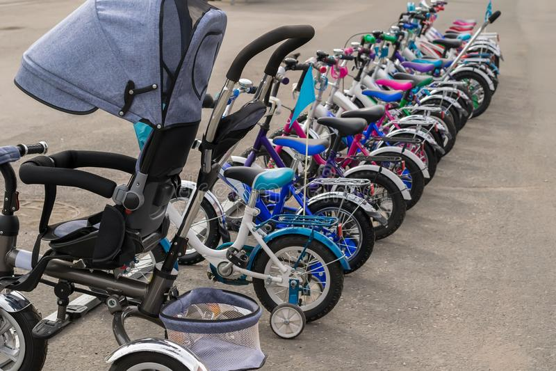 Parking of brand new teenager`s bicycles on asphalt, sale stock photo