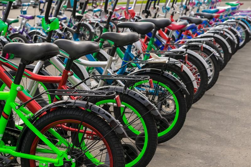 Parking of brand new teenager`s bicycles on asphalt, sale stock photography