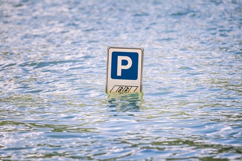 Parking cars road sign partially submerged in a flood. stock photography