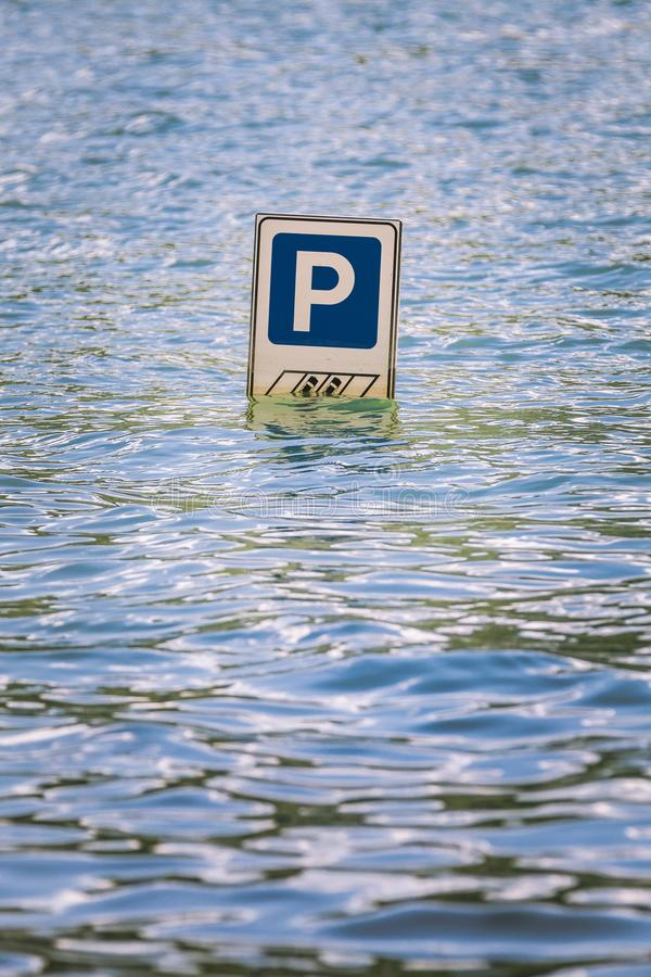 Parking cars road sign partially submerged in a flood. Parking road sign partially submerged in a flood. Letter P indicating parking for cars. Flooding due to stock image