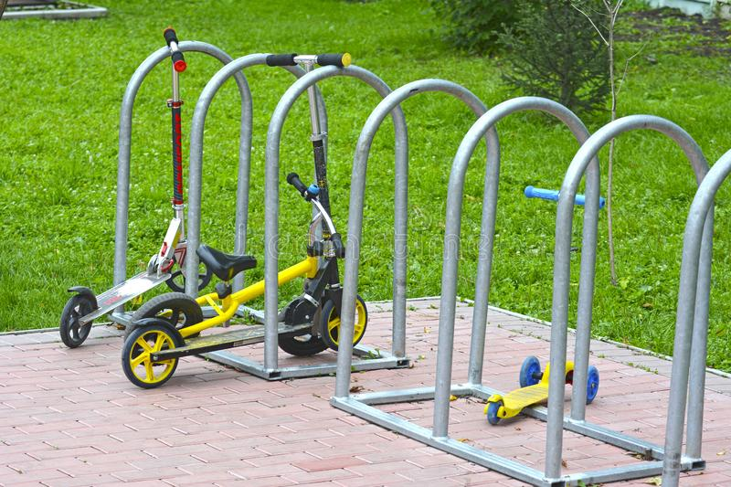 Parking for children`s bicycles and scooters in the park. Summer. stock image