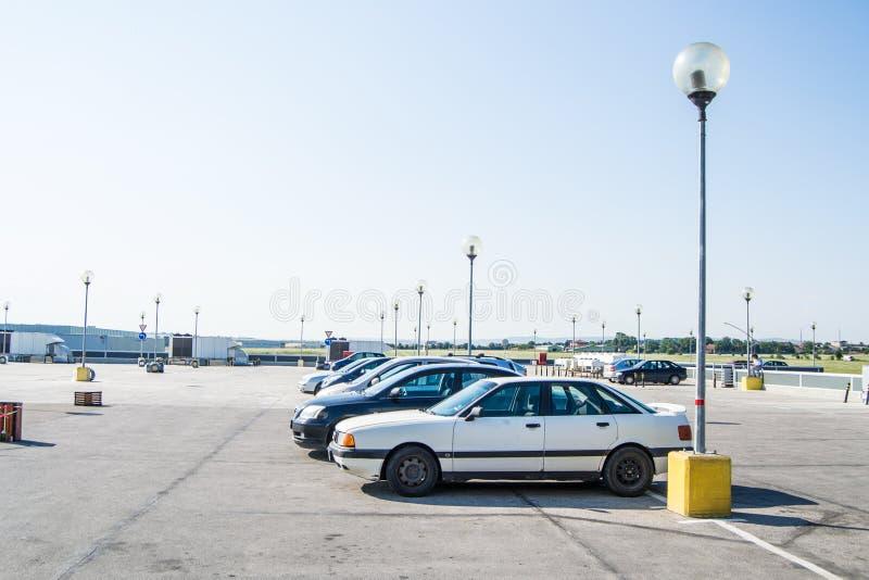 Parking d'un mail avec cinq voitures dans le milieu de la journée photo libre de droits