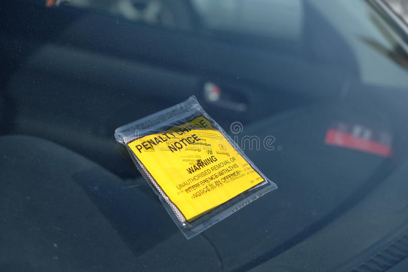 Parking fine penalty notice on windscreen. Yellow sticky notice of parking offence stock photos