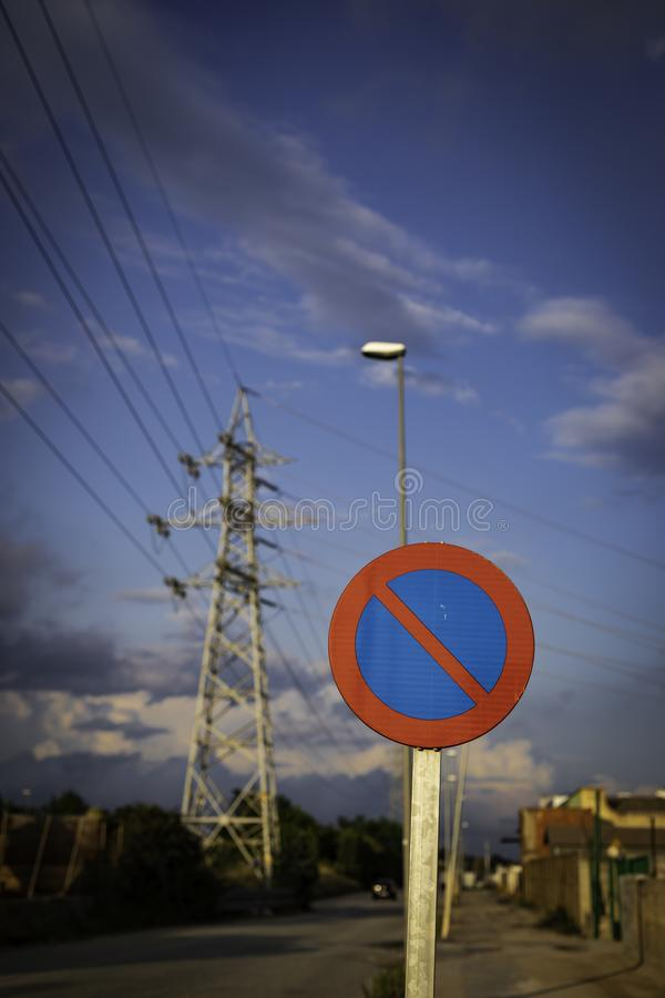 Parking forbidden sign from Spain on a cloudy day with high voltage tower in the background. With copy space, spanish, road, white, street, rule, prohibition royalty free stock images