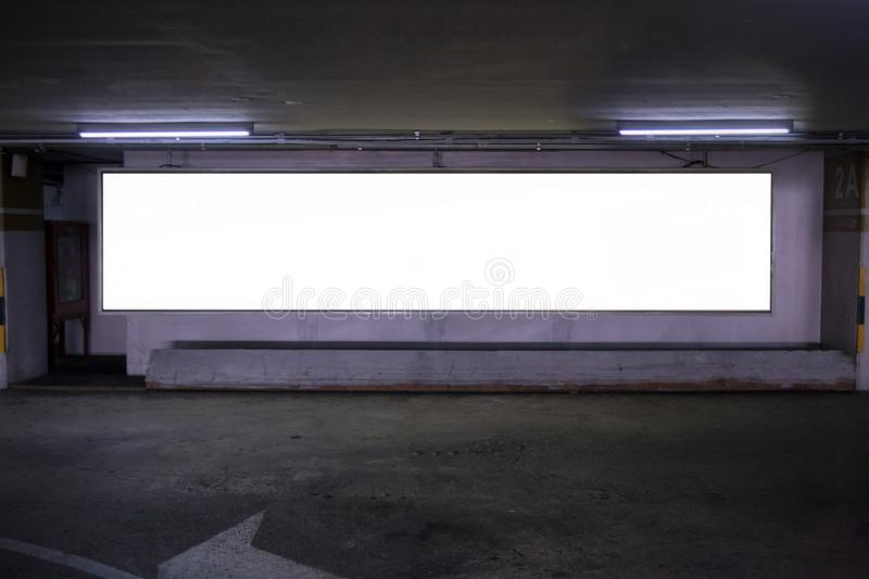 Parking garage underground interior with blank billboard.Empty space car park interior at afternoon.Indoor parking lot. royalty free stock photography