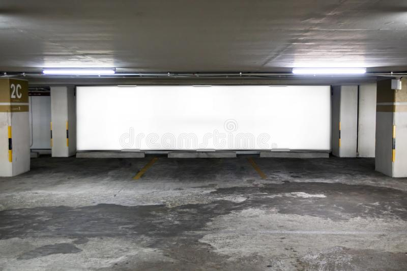 parking garage underground interior with blank billboard.Empty space car park interior at afternoon.Indoor parking lot. royalty free stock image