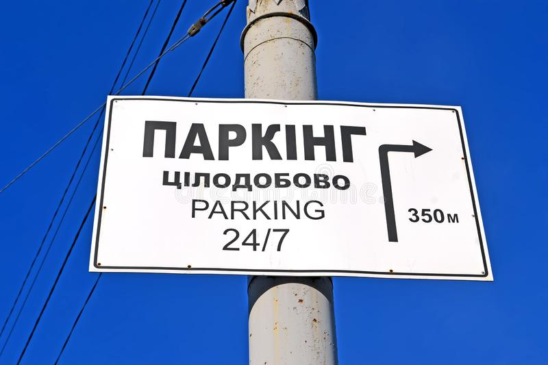 Parking 24 hours as text on ukrainian language on metal pylon on blue sky in sunny day, stock photos