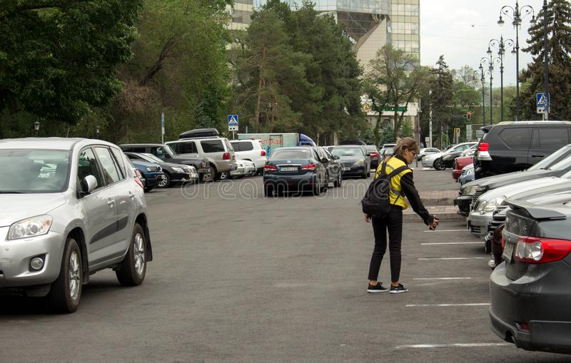 Parking inspector conducts an audit. Almaty, Kazakhstan - 05.23.2018: Tole Bee Street. people in the center of Almaty. Early spring time, parking inspector royalty free stock photo