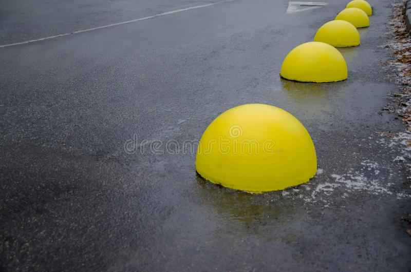 Parking limiter. Concrete balls on asphalt. Yellow concrete balls on asphalt stock photography