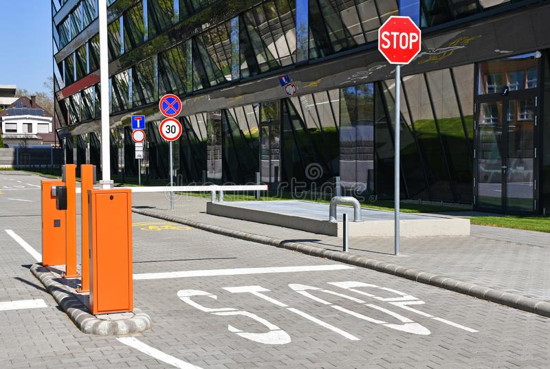 Parking lot gate and stop sign next to an office building stock images