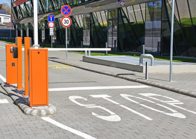 Parking lot gate and stop sign next to an office building stock image