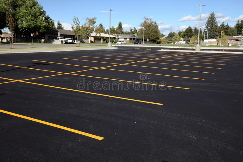 Newly painted yellow stripes create parking stalls in a new parking lot. royalty free stock images