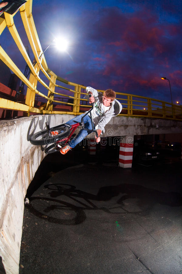 Parking lot wallride. BMX rider performing a trick wall ride against a sunset sky on parking lot royalty free stock images