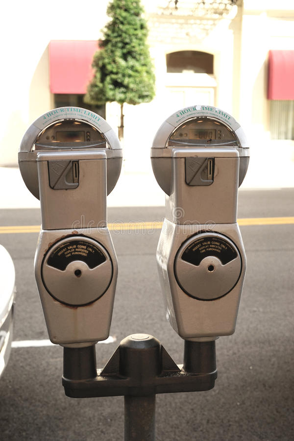Parking meters. Tandem parking meters are often seen in a downtown setting. To avoid fines, it is important to pay the meter stock photos