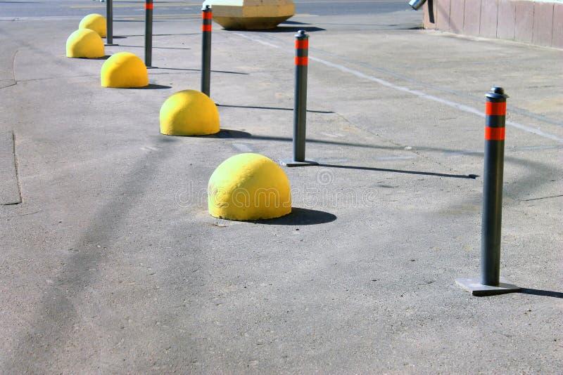 Parking słupy i żółty hemisphereson ulica zdjęcia royalty free