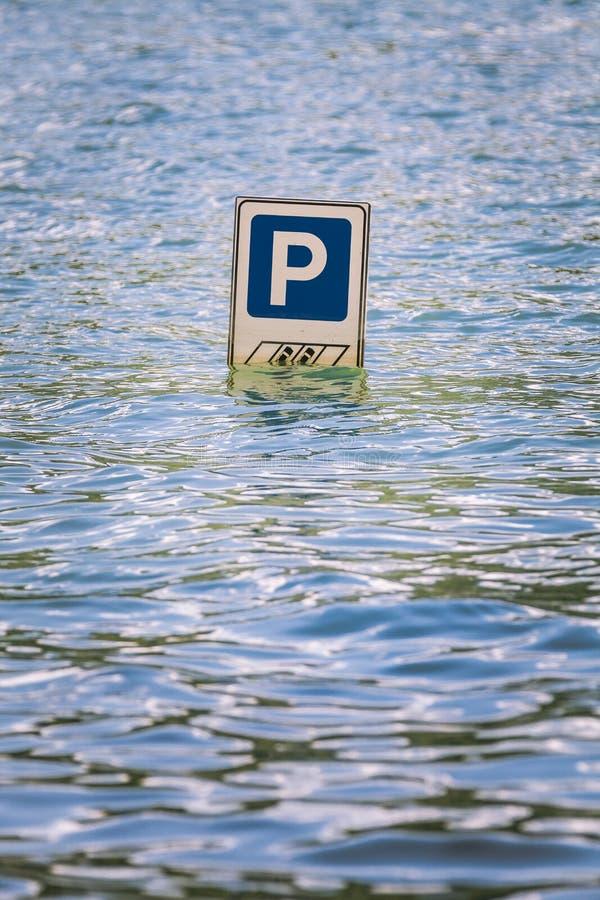 Parking samochodów drogowy znak stronniczo zanurzał w powodzi obraz stock