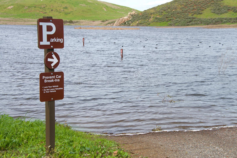 Parking sign pointing to flooded parking lot. Northern California, Coyote Hills parking lot under water, flooded after recent heavy torrential rains royalty free stock photography