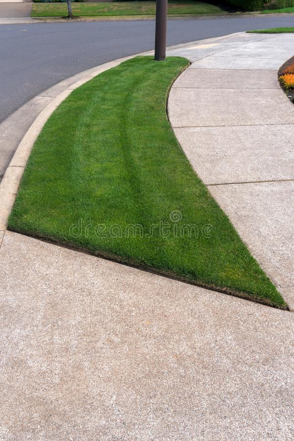 Parking Strip with Green Grass in residential neighborhood. Parking Strip with mowed manicured green grass lawn in suburban neighborhood stock photos