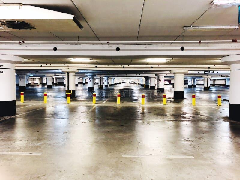 Parking subterráneo interior, luces de neón en el edificio industrial oscuro, construcción pública moderna fotografía de archivo