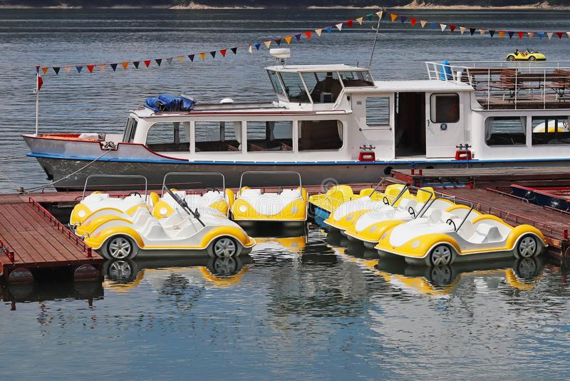 Parking of water bicycles in the form of a car. Toys and attractions are white and yellow. Fun on the water for people. Rest at th. E pond. Travel business stock photo