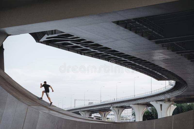 Parkour athlete climbs the bridge. Freerunning in city royalty free stock photos