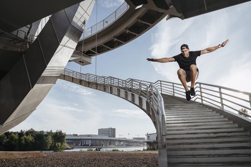 Parkour athlete doing a beautiful high jump from the stairs. Man performing his freerun skill stock image